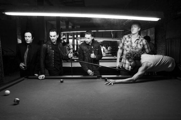 Photograph of members of the band Queens of the Stone Age playing pool