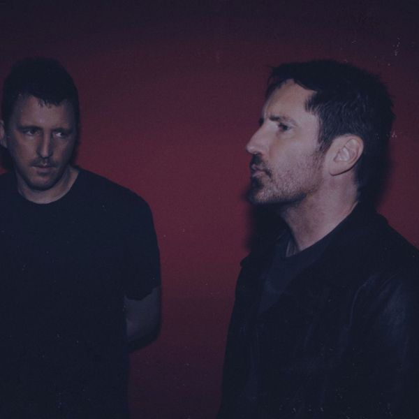 Trent Reznor walking through the desert wearing a black leather jacket and preparing to eat your soul